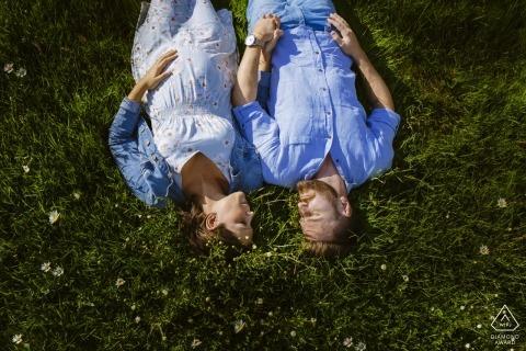 Sesión de fotos de compromiso de una pareja acostada en un campo en Aquisgrán.