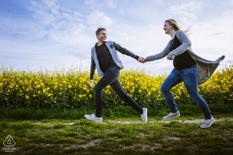 Engagement shoot in Aachen of a couple running through a field of yellow flowers.