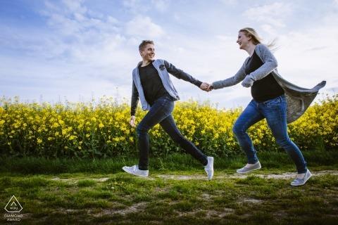 Disparos de compromiso en Aachen de una pareja corriendo por un campo de flores amarillas.