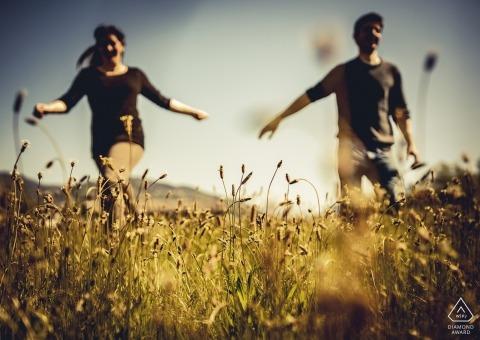 Verlobungsfotosession eines Liebespaares, das durch ein Feld geht, während der Mann in Ceparana nach der Hand seines Verlobten greift.