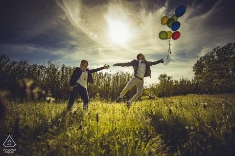 Liebevolle Verlobungsfotosession in Ceparana eines Mannes, der mit einem Bündel Luftballons davonzufliegen scheint, während sein Verlobter nach ihm greift.