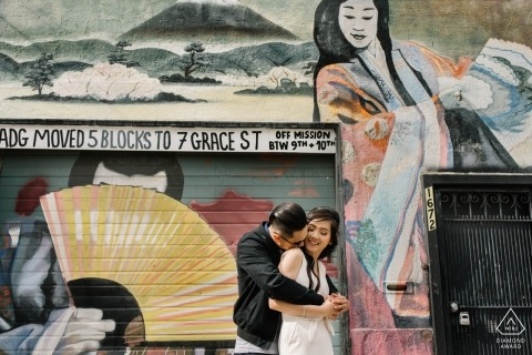 Engagement photo session of a couple standing together in front of a mural in San Francisco.