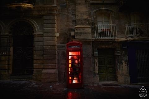 Sesión de retratos de compromiso de Valleta Malta - Una pareja se acurruca en una cabina roja en la noche en Malta