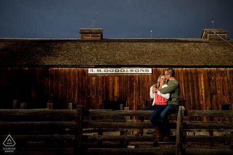 Dodd Lake Engagement Spara con una coppia che si abbraccia su una recinzione durante la loro sessione di fidanzamento in granaio rustico in Colorado