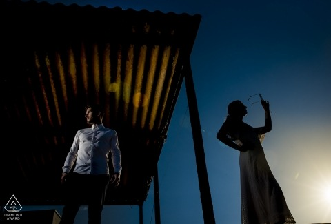 Engagement photo session of a couple standing separately outdoors at dusk in Cabo de Gata.