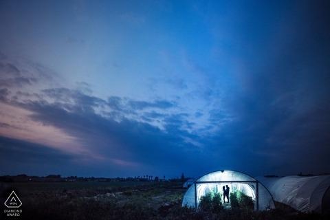 Sesja zdjęciowa zaangażowania pary stojącej w oświetlonej szklarni o zmierzchu w Syrakuzach.