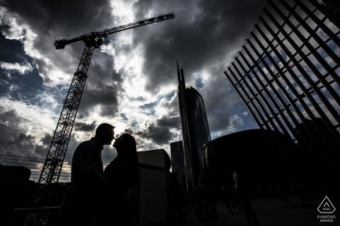 Czarno-białe zdjęcie zaangażowania para silhouetted pod dźwigiem budowlanym w Mediolanie, Włochy.