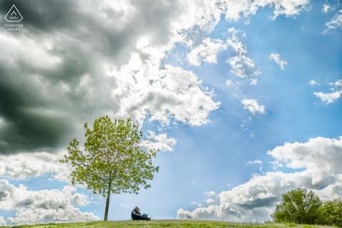 Sessione di foto di fidanzamento di una coppia seduta sulla loro collina accanto a un albero sotto un cielo soleggiato, blu a Saint Martin du Touch, Francia.