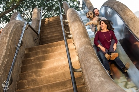 Engagement photo of a couple and their dog going down a slide next to a flight of stairs in Omaha, NE.