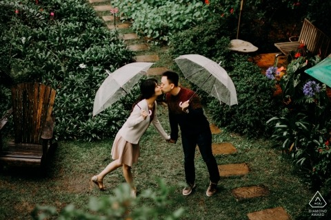 Pre-wedding photo of a couple kissing in the rain as they hold their umbrellas in Da Lat, Vietnam.