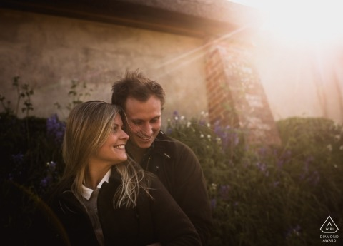 Engagement photo of a couple standing in front of a stone house and flowers as the sun shines down at Broadchalke in Wiltshire, England.