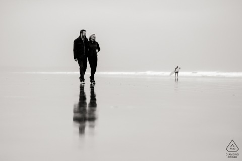 Black and white engagement photo session of a couple walking along Mirror Beach in Devon, England.