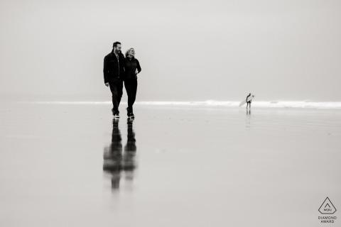 Schwarzweiss-Verpflichtungsfotosession eines Paares, das entlang Spiegel-Strand in Devon, England geht.