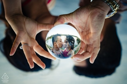 Engagement portrait of a couple kissing reflected in a glass ball they are holding together in El Monte, CA.