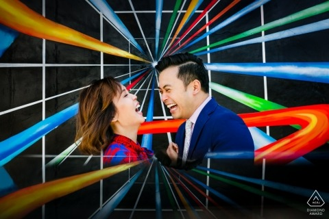 Engagement portrait of a couple laughing surrounded by vibrant, graphic colors in Venice, California.