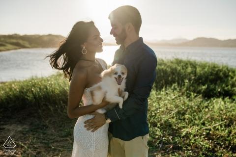 Macae-verlovingsfotoshoot toont het paar dat gelukkig op elkaar lacht terwijl ze hun hond vasthouden
