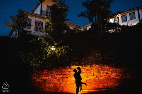 The silhouette man lifting his future bride off her feet were captured in a spot light shining on a stone fence in this Ouro Preto engagement shoot