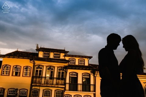 The silhouettes of the couple are captured against a large golden yellow building in this Ouro Preto engagement photo session