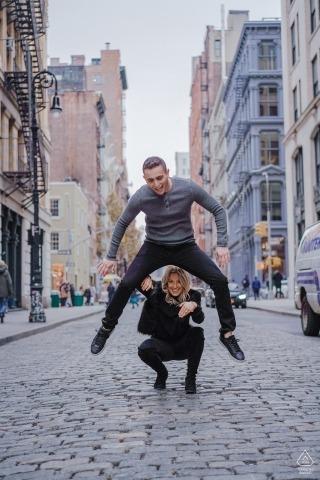 Dieses spielerische Verlobungsporträt der Braut und des Bräutigams, die Bockspringen spielen, wurde auf den Kopfsteinstraßen von Chelsea, NYC gefangen genommen