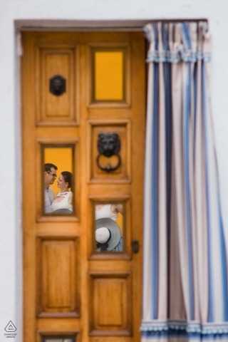 In this Czech Republic engagement photography session, the photographer captures the couple through reflections in an old yellow door
