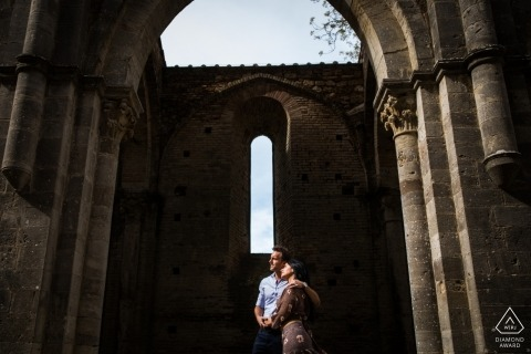 Abbazia di San Galgano engagement portrait of a couple under the arch