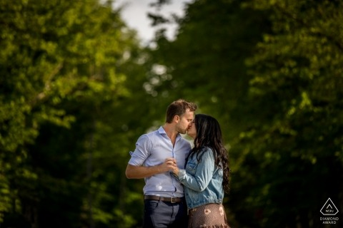 Couple kiss under the lush green trees in this Abbazia di San Galgano engagement photo session