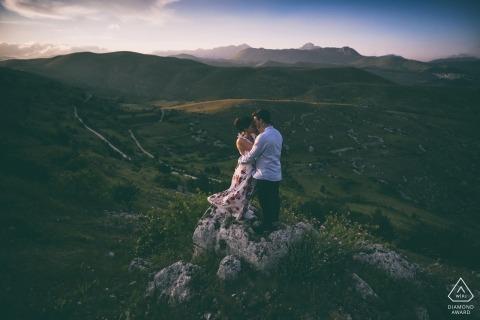 Cette séance de photos de fiançailles entre les Abruzzes et l'Italie montre le couple debout au sommet d'une colline herbeuse alors que des montagnes brumeuses s'éloignent