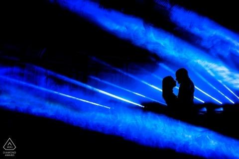 Sylwetki par są uchwycone w mglistym, niebieskim świetle podczas sesji zdjęciowej zaręczynowej w Toskanii