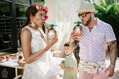 Playa del Carmen, Mexico - de toekomstige bruid en bruidegom drinken een drankje in gouden ananas in deze verlovingsshoot