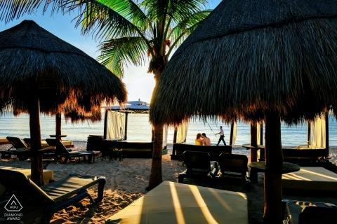 普拉亞德爾卡曼,墨西哥 - 夫婦在這個訂婚照片會議上觀看太陽升起在充滿空的小屋的海灘上