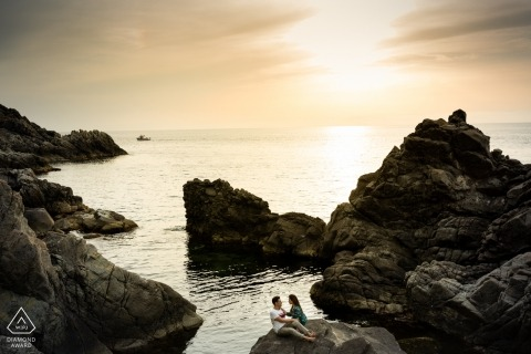 Calabria - the couple lounge on a large boulder next to the ocean as the sun sets behind them in this engagement photo shoot
