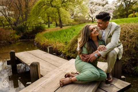 A couple smiles at each other while sitting on a dock during their engagement shoot at Montreal Botanical Gardens