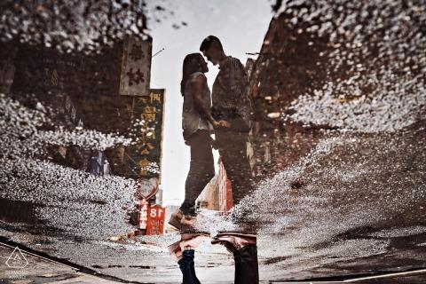 Un riflesso di coppia è catturato in una pozzanghera per strada in questo ritratto di fidanzamento a New York