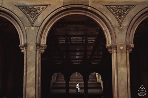 During this engagement shoot, a couple is framed by two sets of large arches while they embrace on the Bethesda Terrace stairs in New York City