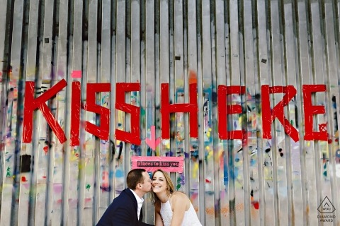 "DUMBO Brooklyn Engagement Session - ""Kiss Here"" gemaltes Schild über küssendem Paar"