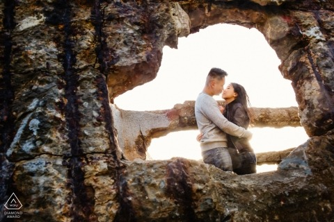 Photographer peeks through a break in the concrete wall to capture the couple embracing in this San Francisco engagement portrait shoot