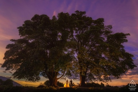 Yun Nan, China pre-wedding photography - couple walking hand in hand under two very large trees while the sky is purple and orange at dusk