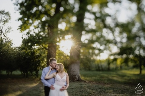 Csengele, Hungary - a man kisses his future bride on her forehead as sun shines through the trees in this engagement photo session