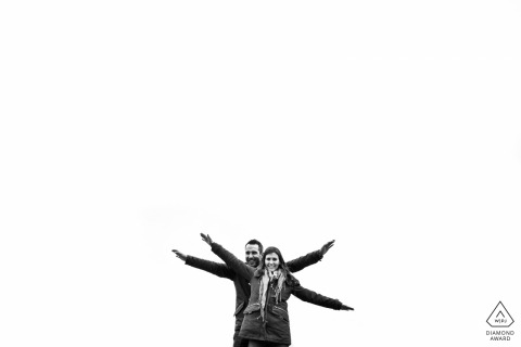 Engagement portrait of a couple with flying open arms and white negative space at Toledo, Castilla-La Mancha (Spain)