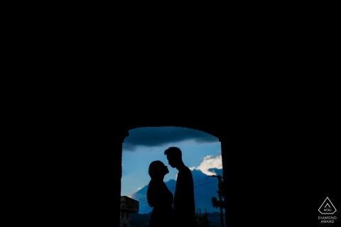 Die Silhouetten des Paares vor einer offenen Tür mit Bergen in der Ferne wurden in dieser Portrait-Sitzung vor der Hochzeit in Fujian, China, aufgenommen
