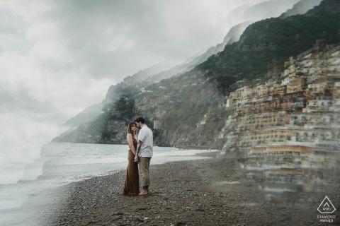 Het echtpaar wordt gezien terwijl ze elkaars hand vasthouden op een druilerig, stenig strand, in deze Naples engagement fotosessie