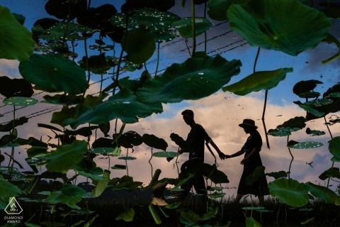 Fuijan, Chine - Des silhouettes du couple heureux marchant main dans la main dans un champ ont été capturées lors de cette séance de portrait précédant le mariage