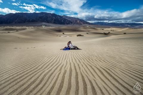 Ein Paar sitzt Rücken an Rücken inmitten einer bergigen Wüste in diesem Verlobungsporträt-Shooting im Death Valley