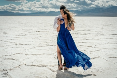 Death Valley engagement shoot takes place in the middle of a desert while mountains stand in the distance behind the embracing couple