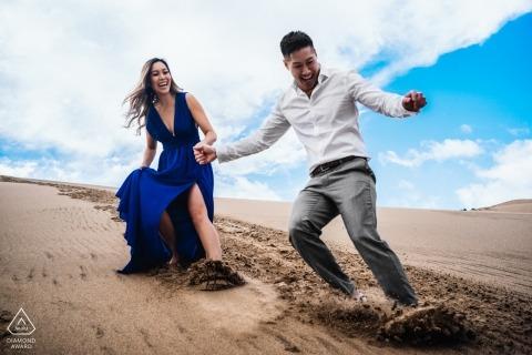 Lachendes Paar der Death- ValleyVerlobungsphotographie schiebt barfuß hinunter Sanddünen unter einen hellen blauen Himmel