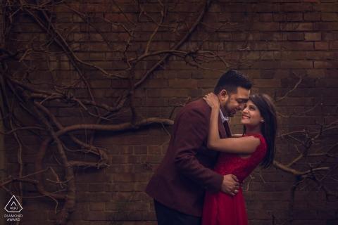 London, UK Verlobung PhotoShoot-Paar lächelt sich glücklich an vor einer Weinrebe bedeckten Mauer