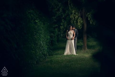 Bath, UK Verlobungsporträt-Shooter umarmt seine zukünftige Braut von hinten, während sie in einem üppig grünen Wald steht