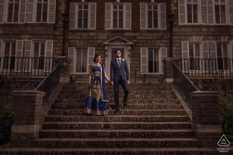 London, UK Verlobungsfotosession. Paar steht Händchenhalten auf Steinstufen, die zu einem großen grauen Gebäude führen