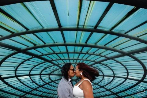 Una pareja se besa debajo de una ventana en espiral y cielos azules en Colombo en esta sesión de fotos de un fotógrafo de bodas de Sri Lanka.