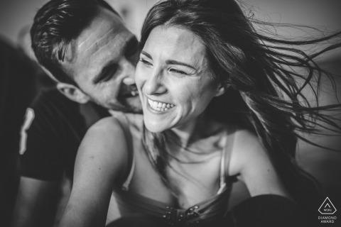 Mężczyzna i kobieta uśmiechają się, pochylając się nad jej ramieniem w czarno-białym portrecie zaręczynowym fotografa z Syrakuz, Sycylii.